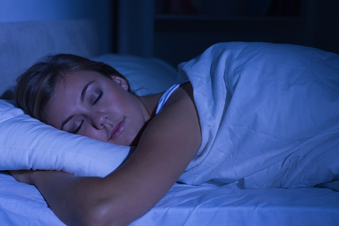 Serene woman sleeping at night in the bedroom